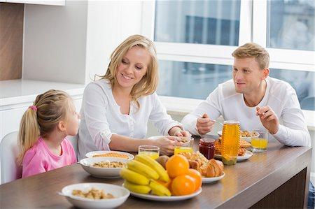 family - Happy family of three having breakfast at table Stock Photo - Premium Royalty-Free, Code: 693-07542219