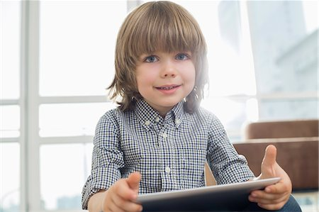Portrait of cute boy holding tablet computer at home Stock Photo - Premium Royalty-Free, Code: 693-07542235
