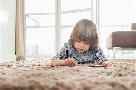 Boy using digital tablet while lying on rug in living room Stock Photo - Premium Royalty-Free, Code: 693-07542231