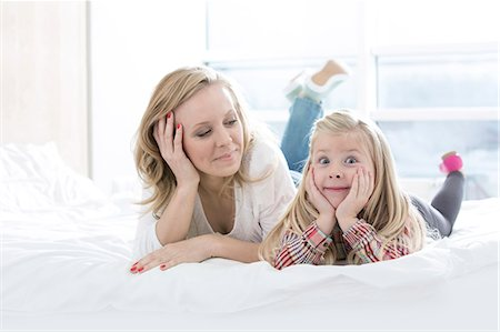 Mother looking at cute daughter making faces while lying in bed Stock Photo - Premium Royalty-Free, Code: 693-07542247