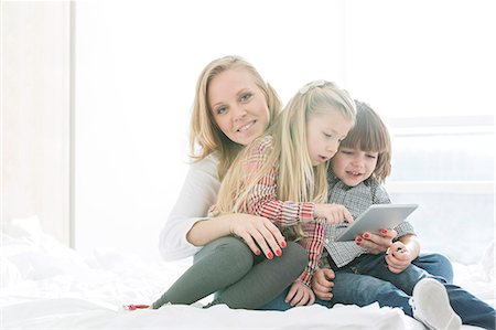 sister - Portrait of happy mother with children using digital tablet in bedroom Stock Photo - Premium Royalty-Free, Code: 693-07542248