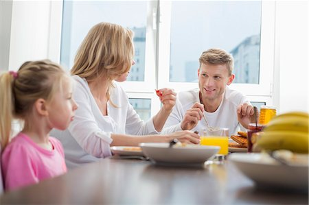 Happy family of three having breakfast at table Stock Photo - Premium Royalty-Free, Code: 693-07542241