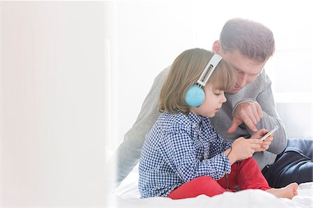 Mid adult father with boy listening music on headphones in bedroom Stock Photo - Premium Royalty-Free, Code: 693-07542254