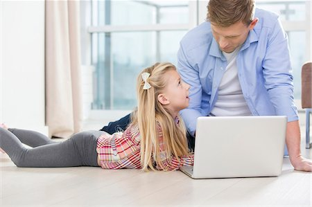 Father and daughter using laptop on floor in living room Stock Photo - Premium Royalty-Free, Code: 693-07542252