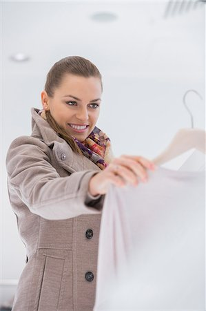 selecting - Happy young woman choosing sweater in store Stock Photo - Premium Royalty-Free, Code: 693-07542281