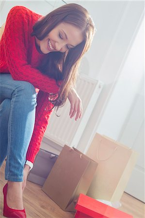 Happy young woman trying on footwear in store Stock Photo - Premium Royalty-Free, Code: 693-07542298