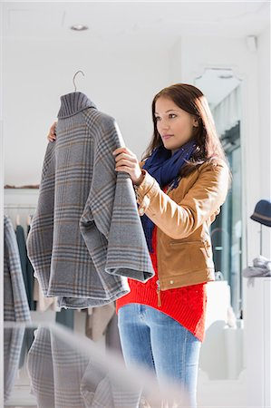selecting - Young woman selecting sweater in store Stock Photo - Premium Royalty-Free, Code: 693-07542290