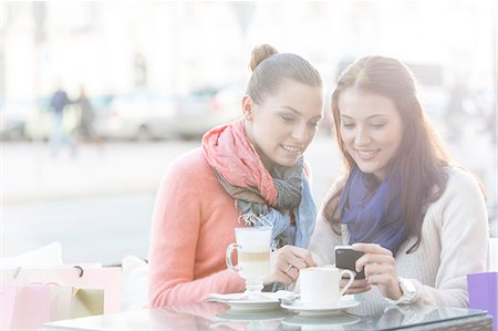 europe coffee shop - Happy women using cell phone at sidewalk cafe during winter Stock Photo - Premium Royalty-Free, Code: 693-07542322