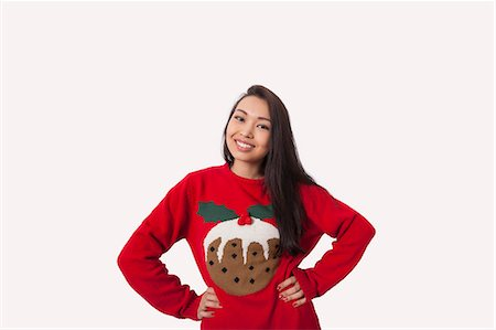 Portrait of woman in Christmas sweater standing with hands on hips over gray background Stock Photo - Premium Royalty-Free, Code: 693-07542365