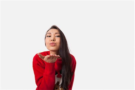 Portrait of woman in Christmas sweater blowing kiss over gray background Stock Photo - Premium Royalty-Free, Code: 693-07542366