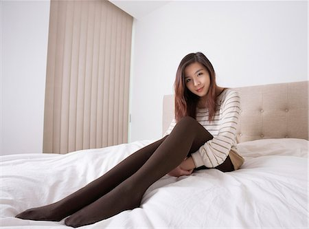 Full length portrait of beautiful young woman in stockings sitting on bed Stock Photo - Premium Royalty-Free, Code: 693-07672539