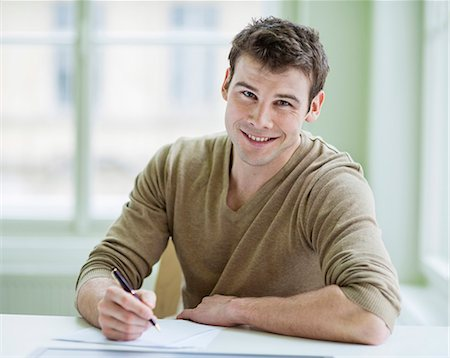 Portrait of handsome businessman writing on document at desk in office Stock Photo - Premium Royalty-Free, Code: 693-07672557