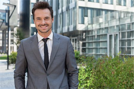 Portrait of smiling young businessman standing against office building Stock Photo - Premium Royalty-Free, Code: 693-07672604