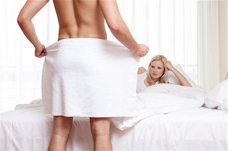 shirtless men - Young woman staring at naked man holding towel in bedroom Stock Photo - Premium Royalty-Free, Code: 693-07672707