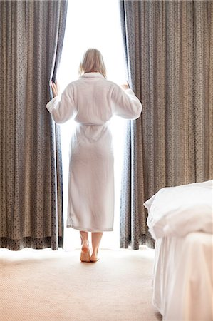 Full length of young woman in bathrobe opening bedroom curtains at hotel room Stock Photo - Premium Royalty-Free, Code: 693-07672725