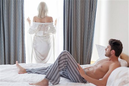shirtless men - Full length of shirtless young man looking at woman standing by hotel window Stock Photo - Premium Royalty-Free, Code: 693-07672727