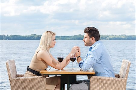 europe coffee shop - Young couple holding hands while looking at each other at outdoor restaurant by lake Stock Photo - Premium Royalty-Free, Code: 693-07672747