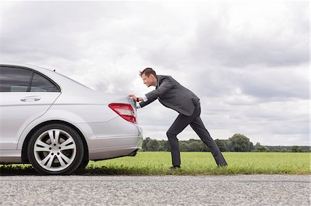 pushing - Full length side view of young businessman pushing broken down car on road Stock Photo - Premium Royalty-Free, Code: 693-07672829