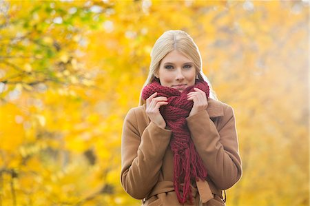 Portrait of beautiful woman holding muffler around neck in park during autumn Stock Photo - Premium Royalty-Free, Code: 693-07672884