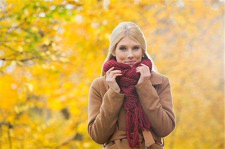Portrait of beautiful woman holding muffler around neck in park during autumn Stock Photo - Premium Royalty-Free, Code: 693-07672884
