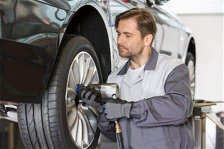 Male mechanic repairing car's wheel in workshop Stock Photo - Premium Royalty-Free, Code: 693-07672918