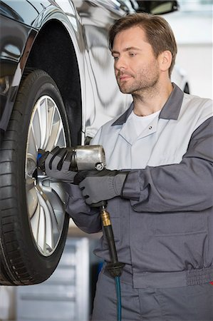 Repairman adjusting car's wheel in workshop Stock Photo - Premium Royalty-Free, Code: 693-07672919