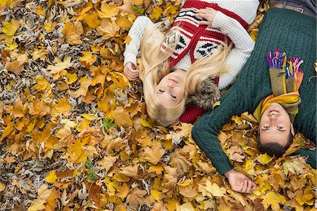 season - High angle portrait of young couple lying on autumn leaves at park Stock Photo - Premium Royalty-Free, Code: 693-07672913
