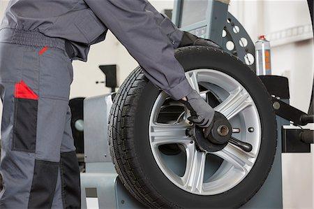 Midsection of male mechanic repairing car's wheel in repair shop Stock Photo - Premium Royalty-Free, Code: 693-07672925