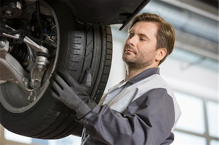 Mid adult technician adjusting car's tire in workshop Stock Photo - Premium Royalty-Free, Code: 693-07672920