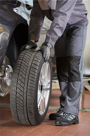 Low section of repairman fixing car's tire in workshop Stock Photo - Premium Royalty-Free, Code: 693-07672922