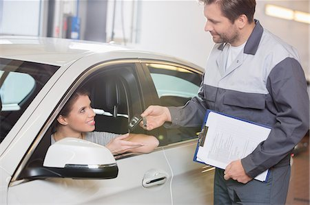 Automobile mechanic giving car key to female customer in workshop Stock Photo - Premium Royalty-Free, Code: 693-07672935