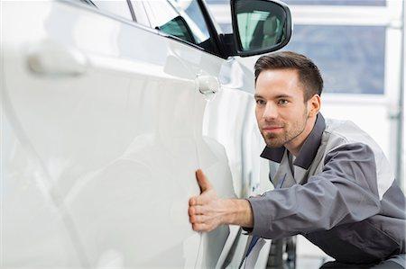 Young maintenance engineer examining car in repair shop Stock Photo - Premium Royalty-Free, Code: 693-07672966