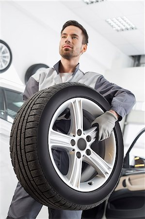 Young maintenance engineer carrying tire in automobile store Stock Photo - Premium Royalty-Free, Code: 693-07672960