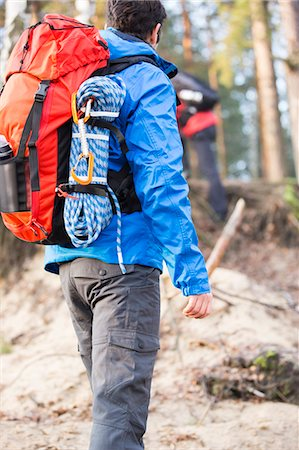 Rear view of male hiker with backpack standing in forest Stock Photo - Premium Royalty-Free, Code: 693-07672997