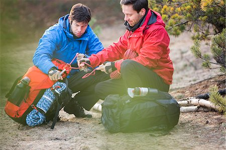 equipment - Male backpackers looking at rope in forest Stock Photo - Premium Royalty-Free, Code: 693-07673008