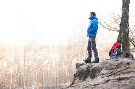 Side view of hiker standing on edge of cliff in forest Stock Photo - Premium Royalty-Free, Code: 693-07673003