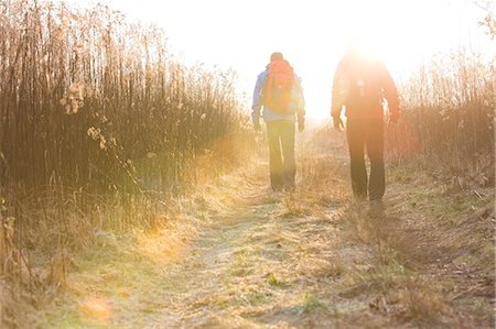 Full length rear view of male hikers walking together in field Stock Photo - Premium Royalty-Free, Code: 693-07673013
