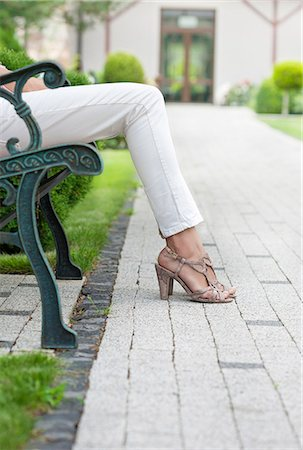 Low section of young woman relaxing on park bench Stock Photo - Premium Royalty-Free, Code: 693-07673051