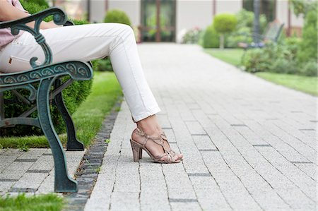 Low section of young woman sitting on park bench Stock Photo - Premium Royalty-Free, Code: 693-07673052