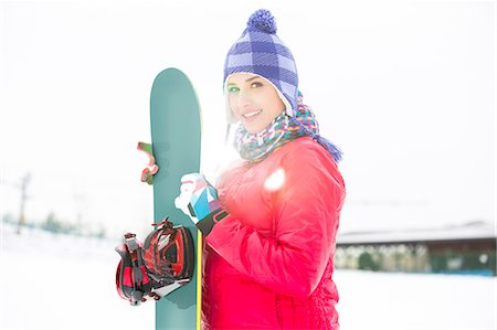 sports and snowboarding - Portrait of beautiful young woman holding snowboard in snow Stock Photo - Premium Royalty-Free, Code: 693-07673076