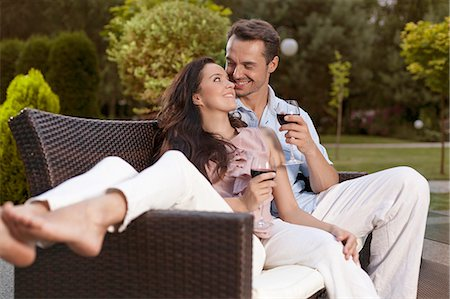 Romantic young holding wine glasses on easy chair in park Stock Photo - Premium Royalty-Free, Code: 693-07673071