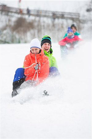 Young couple enjoying sled ride on snow covered slope Stock Photo - Premium Royalty-Free, Code: 693-07673101