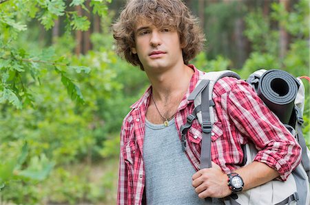 Young male hiker with backpack looking away in forest Stock Photo - Premium Royalty-Free, Code: 693-07673119