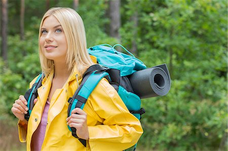 Smiling female backpacker in raincoat looking away at forest Stock Photo - Premium Royalty-Free, Code: 693-07673122