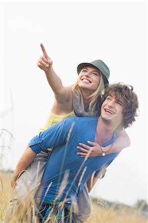 Cheerful woman showing something while enjoying piggyback ride on man in field Stock Photo - Premium Royalty-Free, Code: 693-07673157