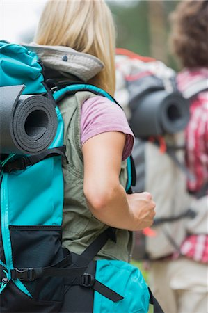 Rear view of female hiker carrying backpack with man in background outdoors Stock Photo - Premium Royalty-Free, Code: 693-07673163