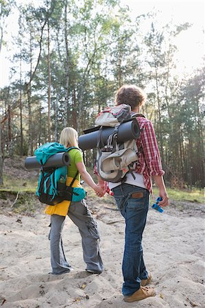 Rear view of hiking couple with backpacks walking in forest Stock Photo - Premium Royalty-Free, Code: 693-07673175