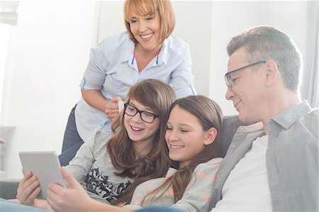 Happy family using tablet PC on sofa at home Stock Photo - Premium Royalty-Free, Code: 693-07673196