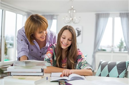 Smiling mother assisting daughter in doing homework at table Stock Photo - Premium Royalty-Free, Code: 693-07673203