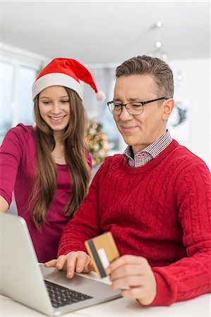 Smiling father and daughter shopping online at home during Christmas Stock Photo - Premium Royalty-Free, Code: 693-07673227